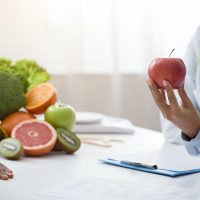 Cropped of nutritionist holding red apple in front of patient